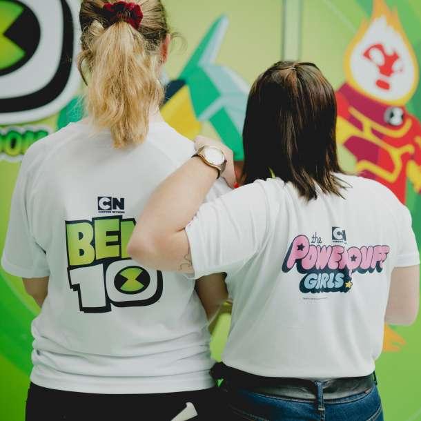 """Promotores de costas a mostrar o vestuário de identificação do evento referentes às séries """"Ben10"""" e """"The Power Puff Girls"""""""